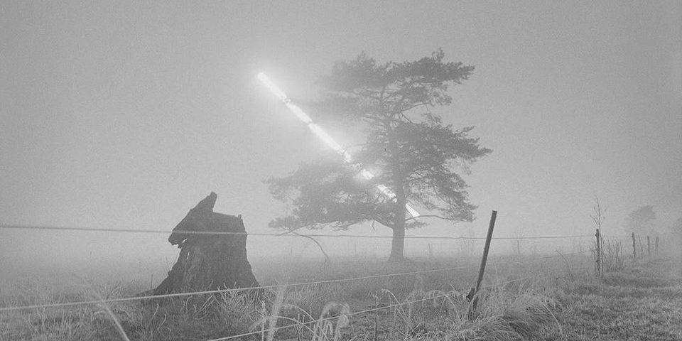 Langzeitbelichtung mit Sonnenverlauf über nebligem Feld