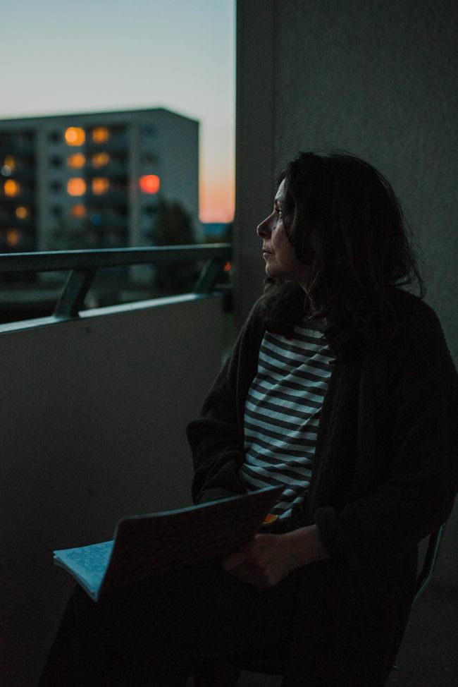 Frau auf einem Balkon in der Dämmerung