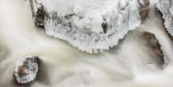 Langzeitbelichtung eines teilweise überfrorenen Flusslaufs