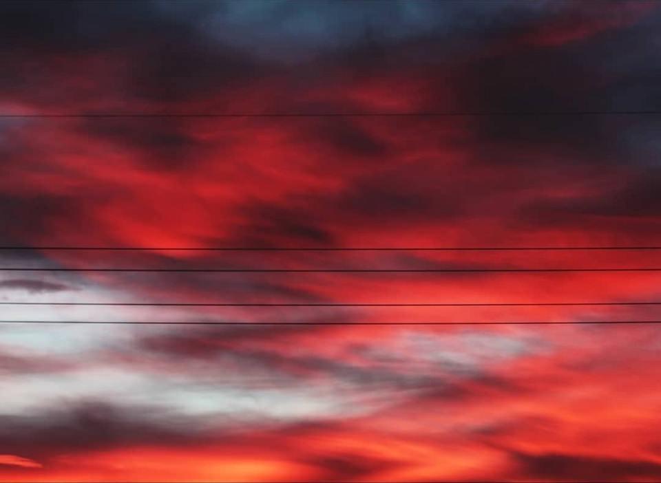 roter Wolkenhimmel mit Stromkabeln