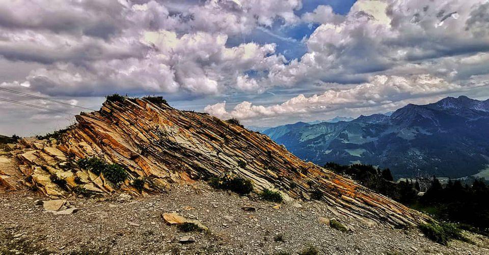Schräg aufgeschichtete Gesteinsschichten vor Berglandschaft mit Wolkenhimmel