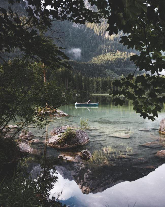 Boot auf Wasserfläche vor einer Berglandschaft