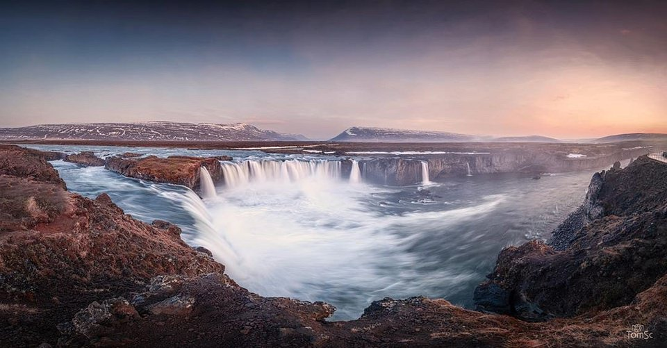 weite Landschaft mit Bergen, Fluss und Wasserfällen