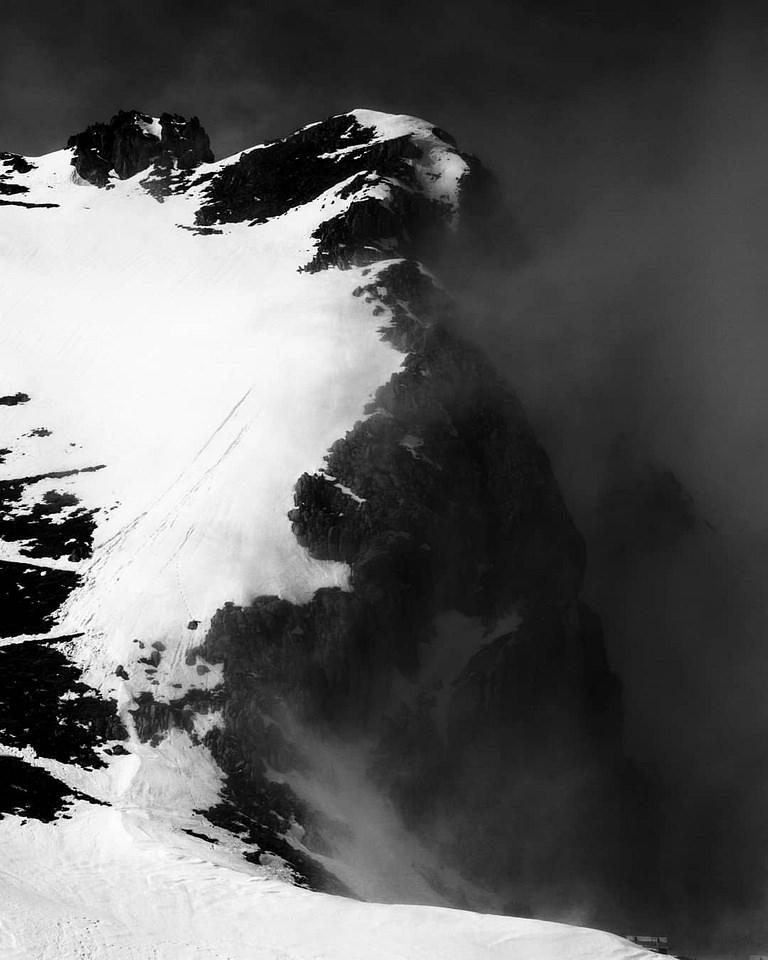 schneebedeckter Berggipfel in Wolken