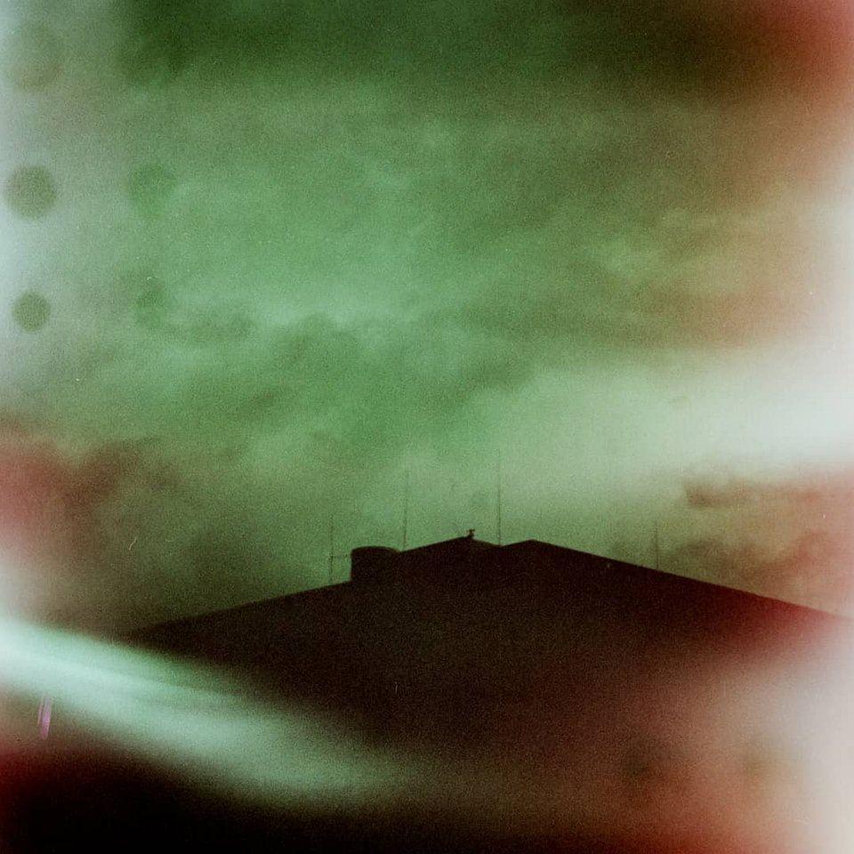 grünrotes Bild eines Hausgiebels vor Wolkenhimmel mit analogen Bildfehlern