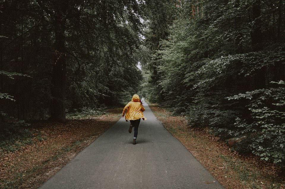 Mensch rennt auf einem Waldweg