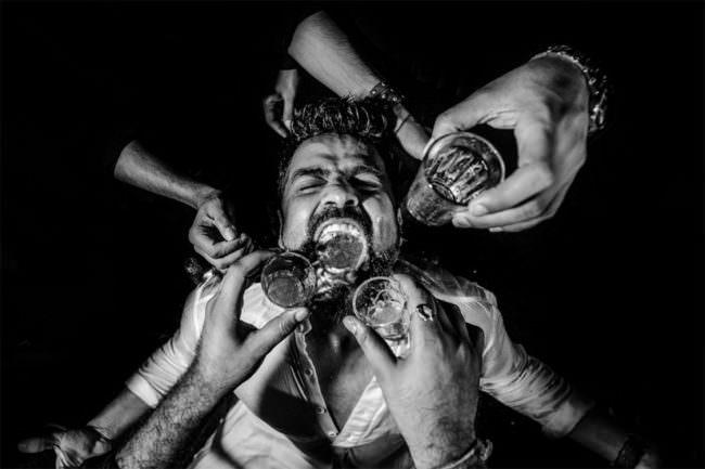 Ein Mann bekommt Getränk in den Mund geschüttet