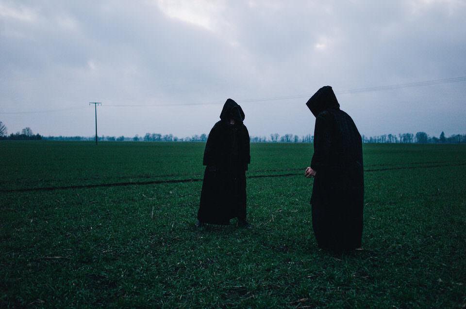 Zwei Personen in schwarzer Kutte
