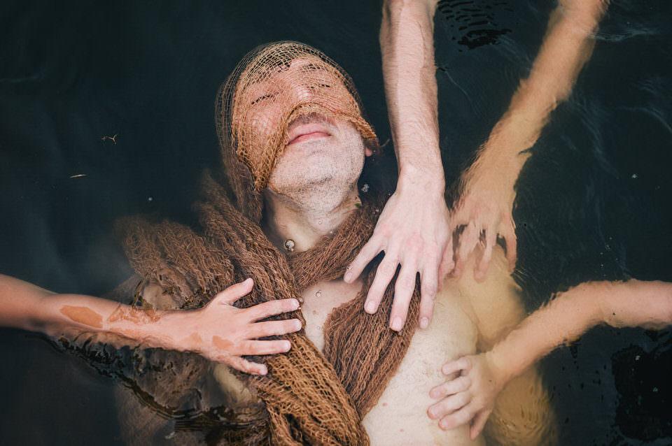 Mann im Wasser mit Händen auf der Brust