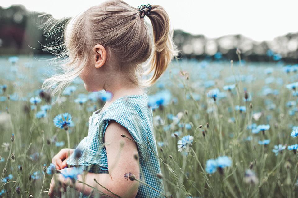 Kind in einer Blumenwiese