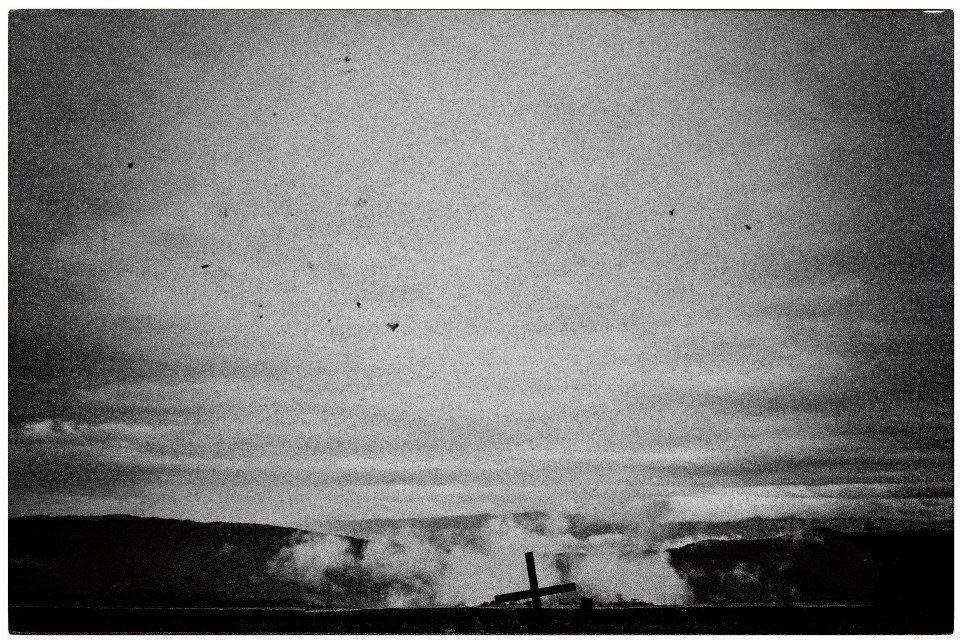 Kreuz im Qualm und Vögel am Himmel