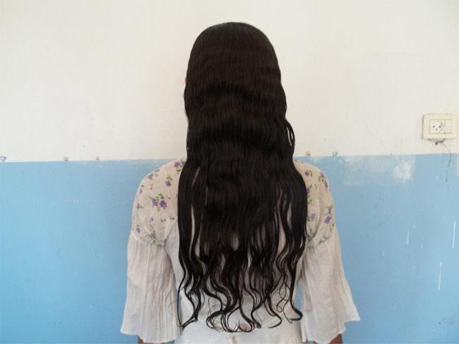 Person mit langen schwarzen Haaren vor einer Wand