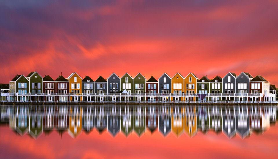 Bunte Häuser spiegeln sich im Wasser im Sonnenuntergang