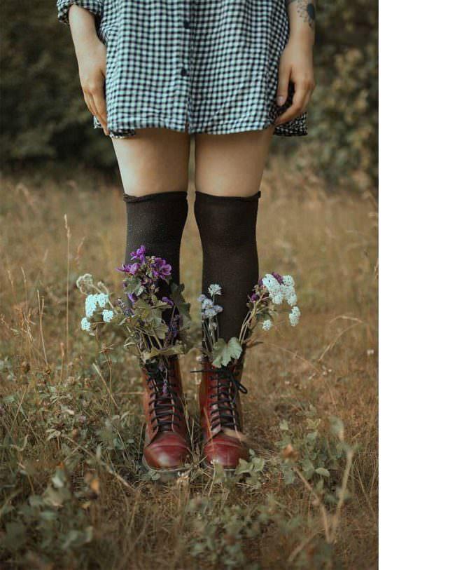 Beine mit wilden Blumen in den Stiefeln