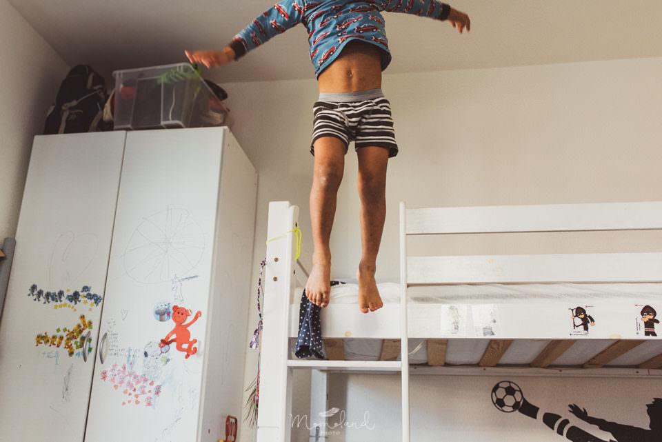 Kind springt vom Bett