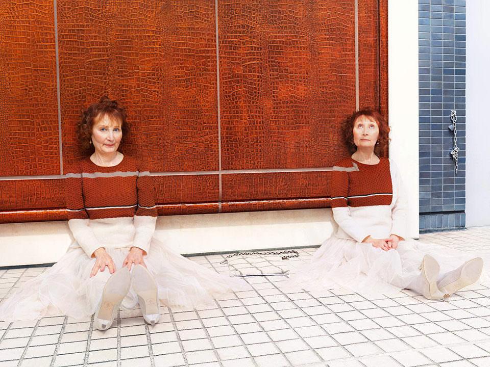 Zwei Frauen mit Pullovern, die zur Wand passen