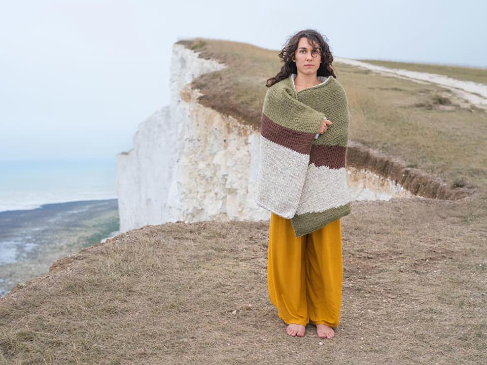 Frau mit Decke an einer Klippe
