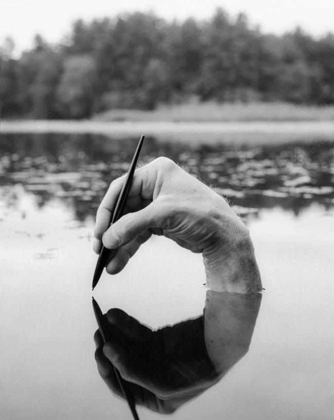 Hand mit Stift im Wasser