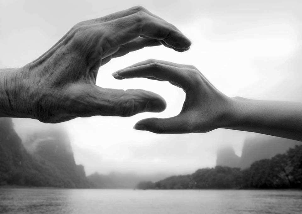 Zwei Hände greifen nach einander vor einem See