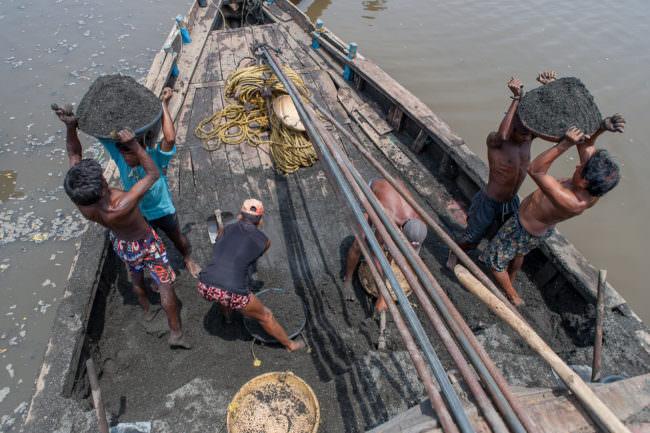 Menschen auf einem Boot mit schwarzem Sand