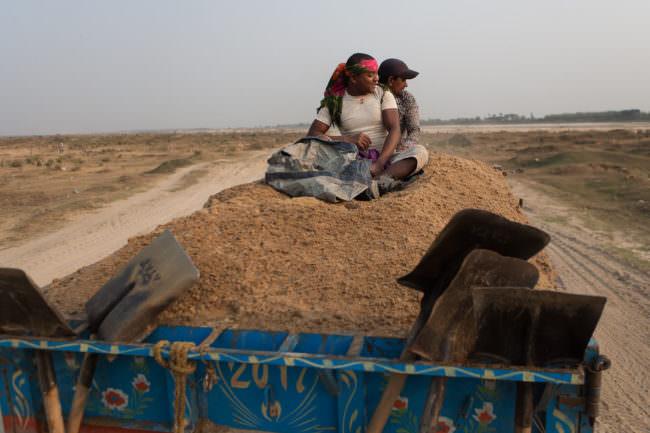Zwei Arbeiter fahren auf einem mit Sand befüllten Anhänger