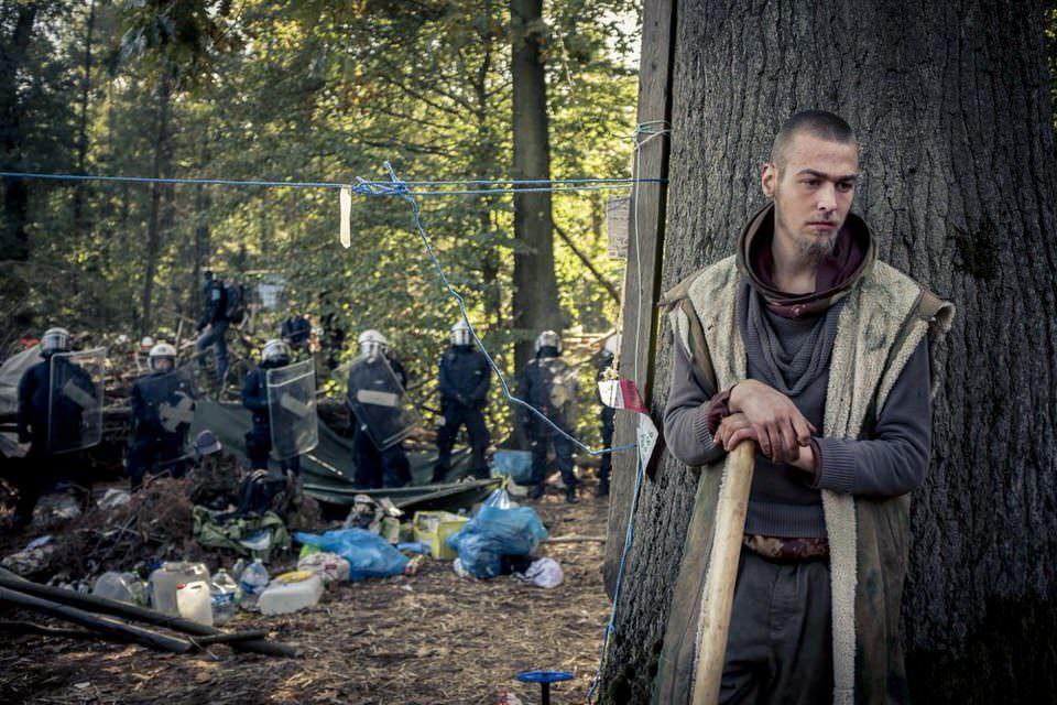 Mensch hinter Baum. Im Hintergrund Polizei