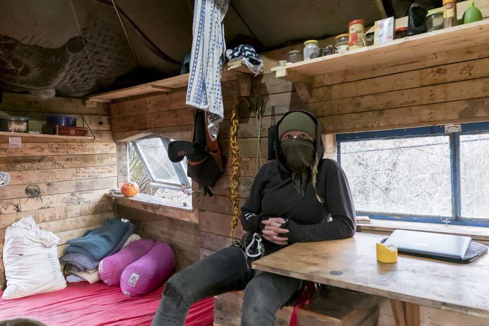 vermummter Mensch im Baumhaus