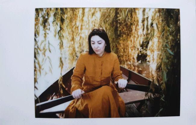 Frau im Ruderboot unter einer Weide
