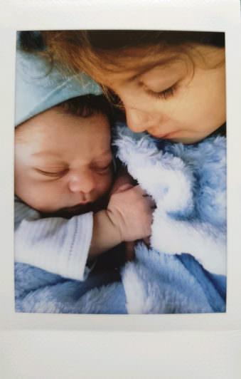 Kind und Baby kuscheln