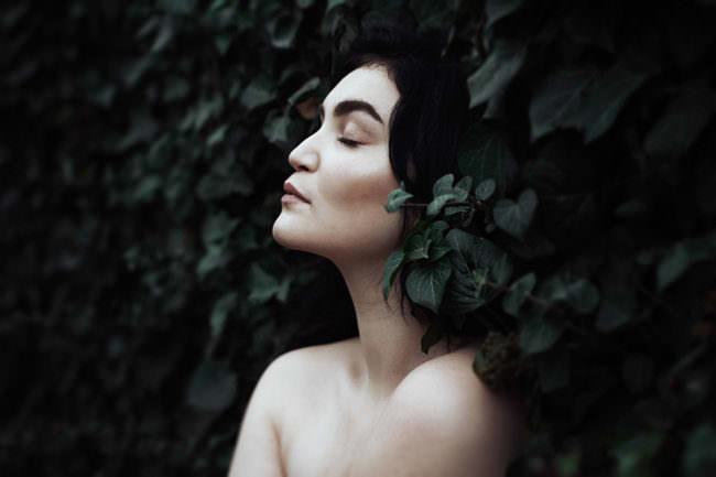 Frau zwischen Efeu