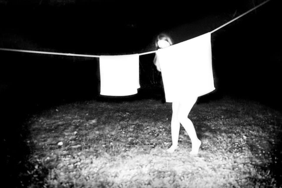 Frau versteckt sich hinter Wäsche