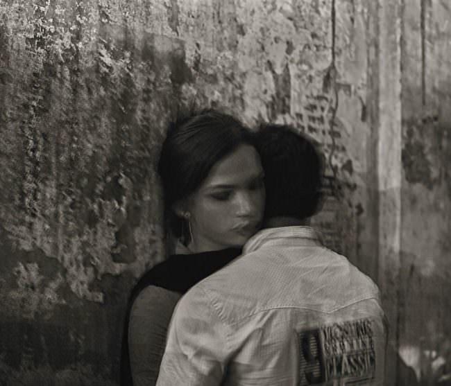 Zwei Mesncehn umarmen sich an einer Mauer