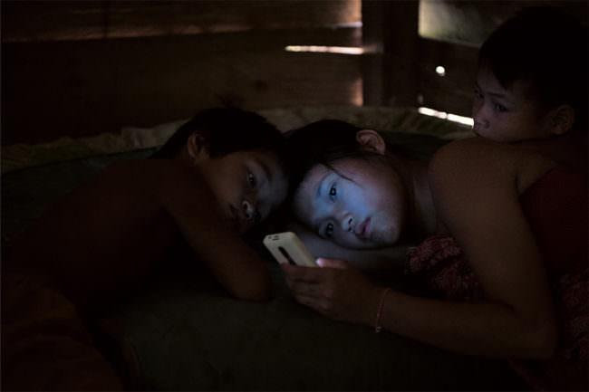 Eine Frau mit zwei Kindern schauen ins Handy