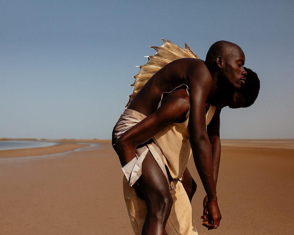 Mann trägt anderen Mann mit Rückenflosse auf dem Rücken