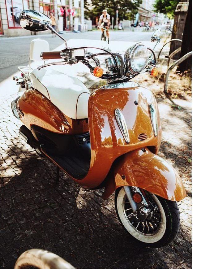 oranger Motorroller am Straßenrand