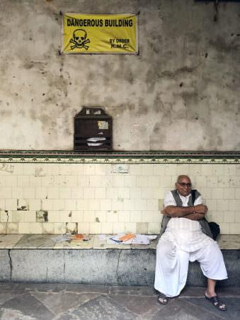 Mann vor einem Warnschild sitzend