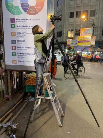 Fotografin bei der Arbeit auf einer Leiter