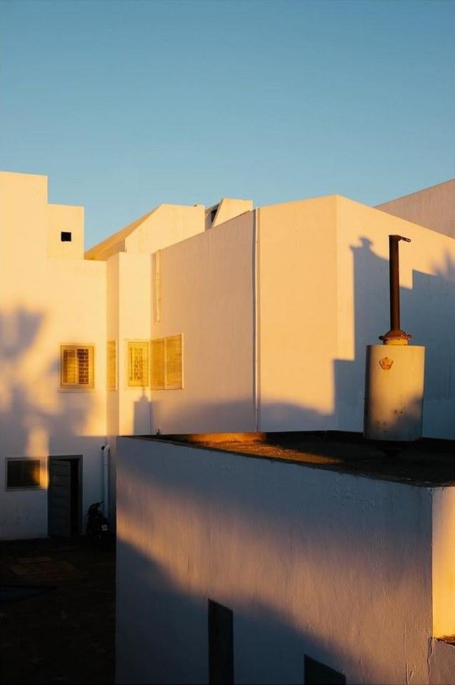 goldenes Licht und blaue Schatten auf weißen Hauswänden