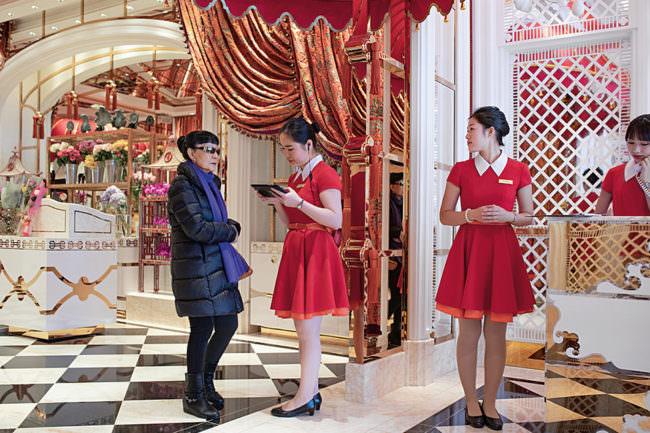 Zwei Frauen in roten Kleidern begrüßen eine Frau