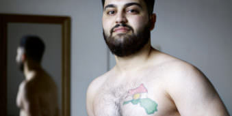 Junger Mann mit Oberkörper frei, auf diesem befindet sich ein Tattoo