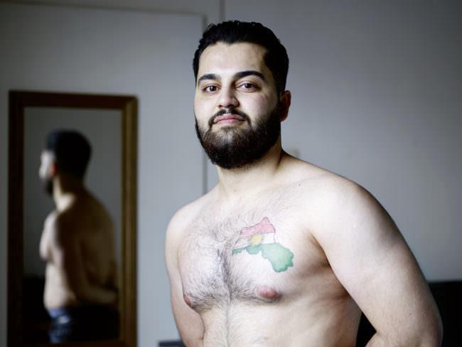 Junger Mann mit freiem, tätowierten Oberkörper