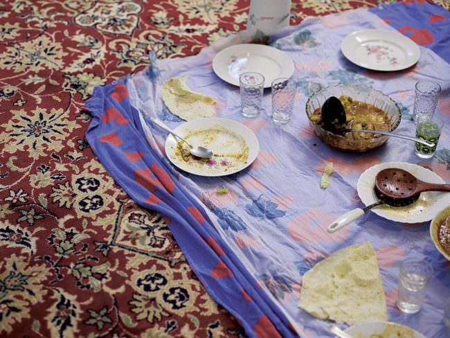 Farbenfroher Teppich mit Tuch und Essgeschirr