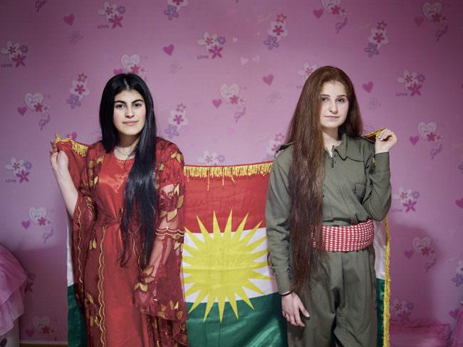 Zwei Frauen halten eine Fahne vor bunter Tapete