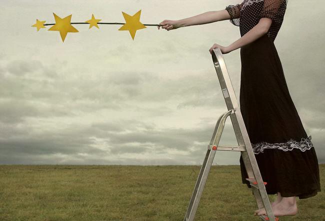 Mädchen steht auf einer Leiter und hält gebastelte Sterne in den Himmel