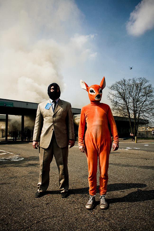 Mann mit Maske und Verkleideter Mensch auf der Straße. Im Hinergrund steigt Rauch aus