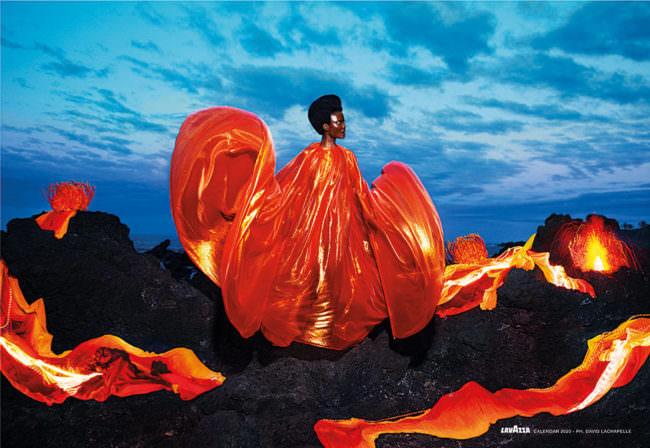 Frau auf Felsen mit einem Kleid, das nach Feuer aussieht