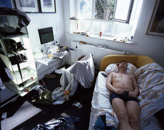 Mann liegt auf der Couch in einem chaotischen Zimmer