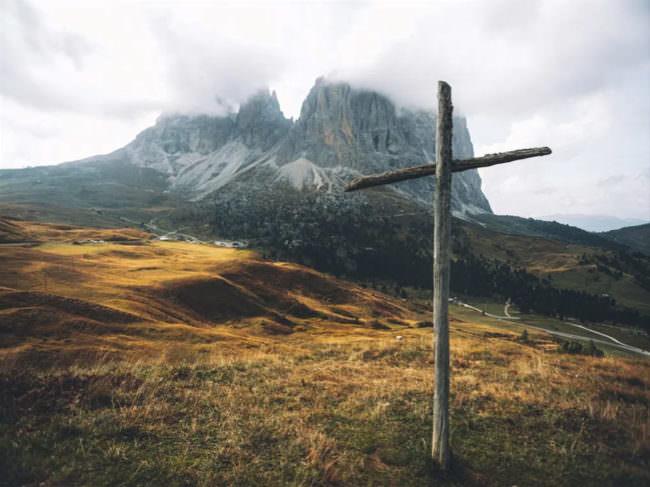 Ein Holzkreuz im Vordergrund, im Hintergrund Berge