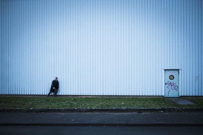 Mann lehnt an einer großen Wand