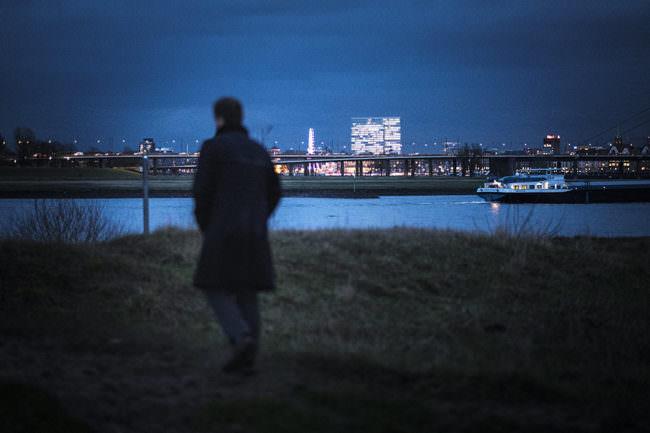 Mann auf einer Wiese vor einer Großstadt